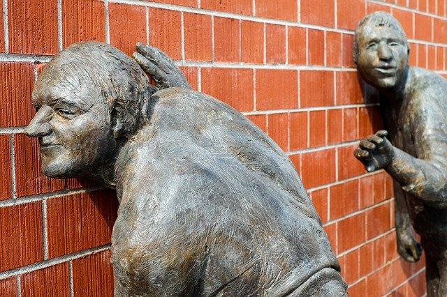 A sculpture of men with ears pressed to a brick wall - Image by Couleur from Pixabay